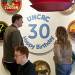 """Young people talking beside a shield reading """"UNCRC Happy Birthday 30"""""""