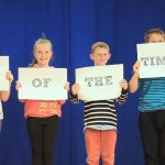 """Children holding up signs which say """"Sign of the times"""""""
