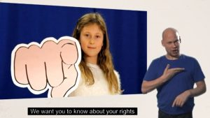 Young girl with cardboard hand in a pointing shape with sign language interpreter next to her.