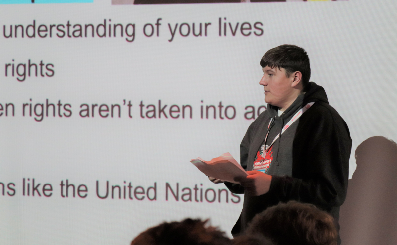 A young person stands in front of a screen explaining something to a crowd. It's clear from the text on the screen behind him that he is talking about rights.
