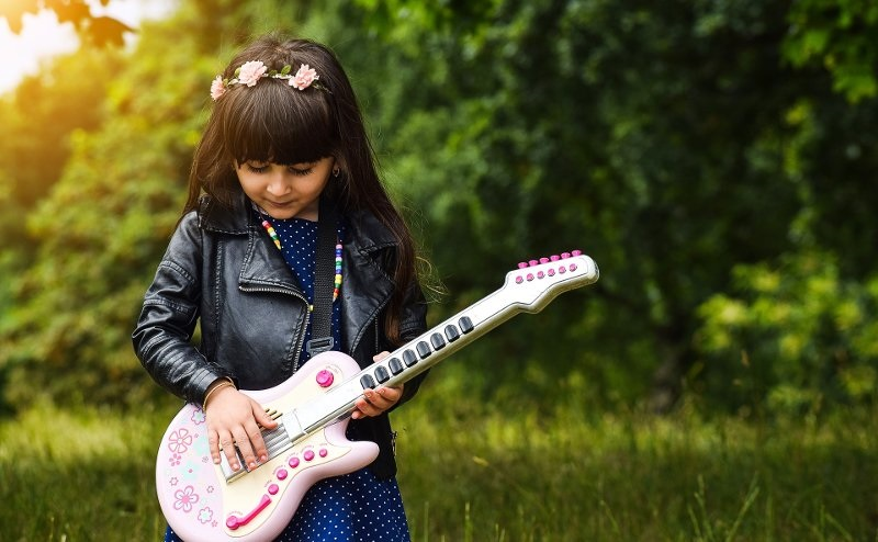 Picture of a girl playing with a toy guitar.