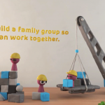 """A screencap showing Plasticine men constructing something with a toy crane, with a caption above them: """"Let's build a family group so we can work together."""""""