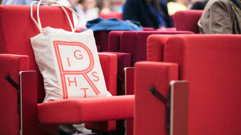 "An image of a tote bag with the word ""Rights"" on it sitting on a chair in .a lecture theatre"