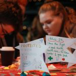 Two young people working at a craft table, while in front of them are flags other young people have made illustrating different human rights they have.