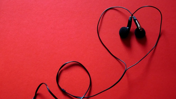 Headphones on a red background, their wires arranged to form the shape of a heart.