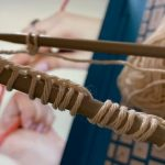 A close up of knitting needles as hands wrap string behind them.