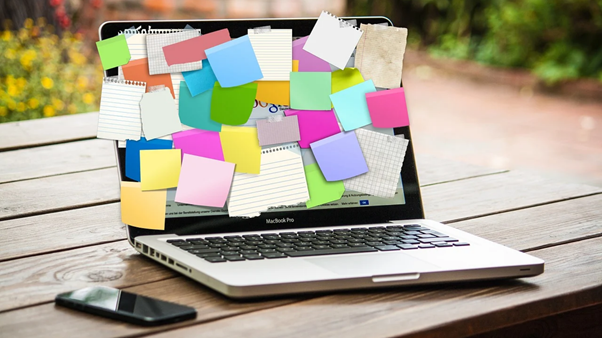 An image of a laptop covered in notepad paper and post-it notes.