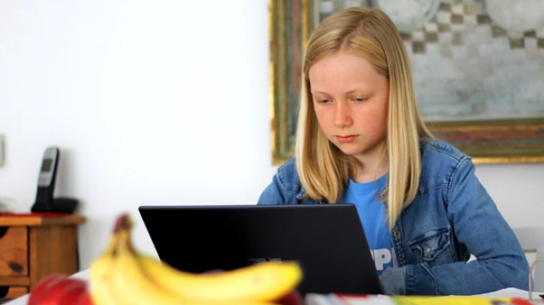 A girl looking at her open laptop on a table in what looks like her home.