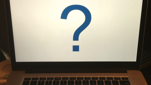 An open laptop with a question mark on the screen, illustrating the concept of an online quiz.