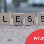 """Scrabble tiles spelling out the word """"LESS"""" beside a plastic toy house. Image has the caption """"Poverty."""""""
