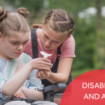 """A girl in a wheelchair looking at a small piece of paper along with another girl. Image has the caption """"Disability and ASNs."""""""