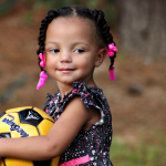 A girl smiling and holding a football.